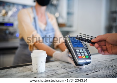 Contactless payment with debit card, coffee shop open after lockdown.