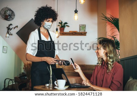 Contactless payment with mobile in restaurant. Waitress standing, wearing protective face mask and smiling customer with her mobile on hand about to pay. It's daytime during Coronavirus pandemic