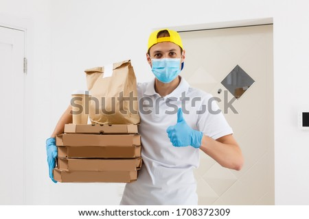 Contactless Pizza delivery. Pizza box. Delivery man holding cardboard boxes in medical rubber gloves and mask. Fast and free Delivery transport . Online shopping and Express delivery . Quarantine