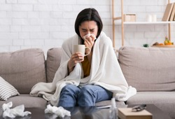 Contagious disease outbreak. Sick girl with hot drink suffering from virus at home