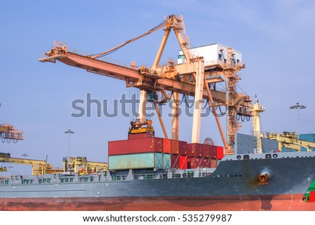 Container Cargo freight ship with working crane bridge in shipya