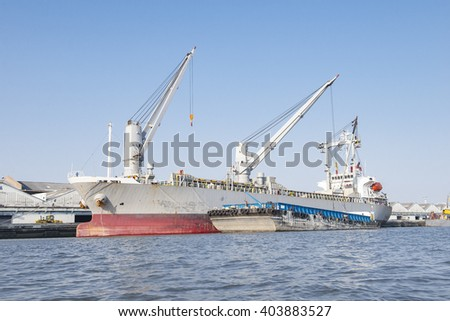Container Cargo freight ship with working crane bridge in shipyard at evening. #403883527