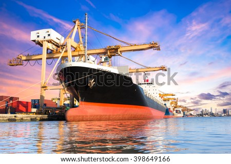 Container cargo freight ship with working crane loading bridge in shipyard at twilight for logistic Import export background