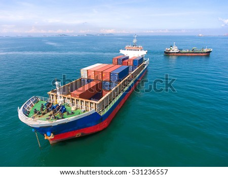 container,container ship in import export and business logistic.By crane , Trade Port , Shipping.Tugboat assisting cargo to harbor.Aerial view.Water transport.International.Shell Marine.
