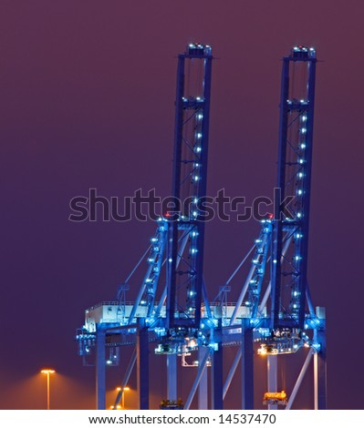Container cranes in the Port of Rotterdam against purple night sky