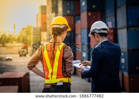 Container Depot chief talking to female foreman about custom document of the goods inside Empty Container depot in Broad daylight Foto stock ©
