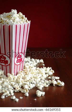 Container full of pop corn and few on a table