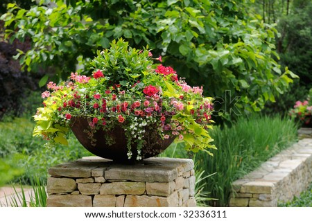 Container Garden on Stone Wall. Metal planter with geranium, calibrachoa (million bells) and sweet potato vine adding curb appeal to house entrance #32336311
