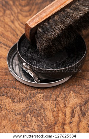 container of shoe polish and brush on wooden background