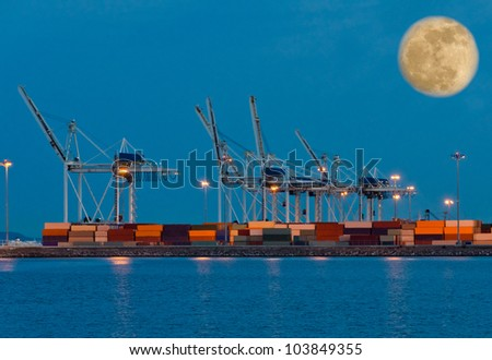 Container port terminal at night ( dawn, dick ) time with big moon in the sky.