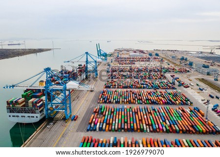Container port with large ship being loaded and unloaded with gantry crane. International shipment and global freight transport and commerce. Aerial view of cargo harbor wharf. Stockfoto ©
