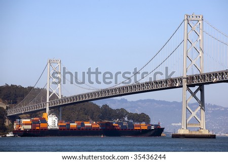 Container Ship and Bay Bridge - stock photo