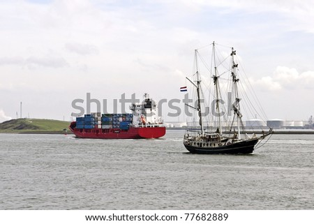 container ship and sailboat on there way to the sea