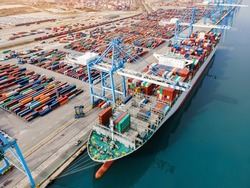 Container ship being loaded and unloaded at terminal freight port, international shipping and global commerce, modern cargo harbor and yard for maritime shipment and delivery, worldwide transport.