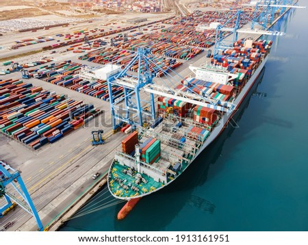Container ship being loaded and unloaded at terminal freight port, international shipping and global commerce, modern cargo harbor and yard for maritime shipment and delivery, worldwide transport. Stockfoto ©