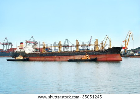 Container ship coming into port with tugboats