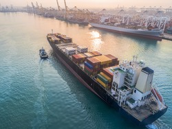 container ship commercial vessel arrival to the port channel due, assist by the tugs boat for safety entrance at gateway of the international port worldwide logistics services
