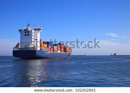 Container ship departs from a port in the sea.