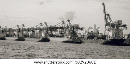 container ship entering port with sunset time,Image blur is tone black and white