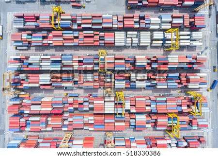 container ship in import export and business logistic.By crane , Trade Port , Shipping.Tugboat assisting cargo to harbor.Aerial view.