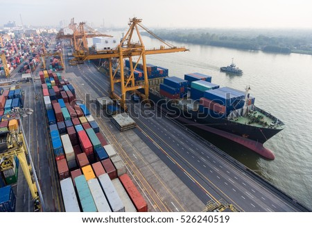 container ship in import export and business logistic.By crane , Trade Port , Shipping.Tugboat assisting cargo to harbor.Aerial view.In Thailand.