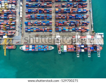 container ship in import export and business logistic.By crane , Trade Port , Shipping.Tugboat assisting cargo to harbor.Aerial view.International Investment.transaction.