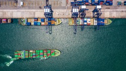 Container ship loading and unloading in deep sea port, Aerial top view of logistic import export transportation business by container ship in open sea.