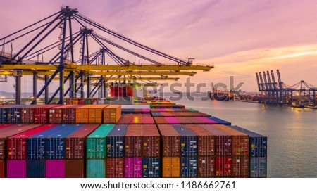 Container ship loading and unloading in deep sea port at sunset, Business logistic import and export freight  transportation by container ship in open sea, Industrial crane cargo freight ship.
