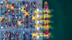 Container ship working at night, Business import export logistic and transportation of International by container ship in the open sea, Aerial view industrial crane loading cargo freight port, Dubai.