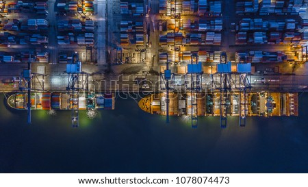 Container ship working at night, Business import export logistic and transportation of International by container ship in the open sea, Aerial view.