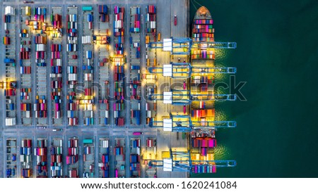 Container ship working at night, Business import export logistic and transportation of International by container ship in the open sea, Aerial view industrial crane loading cargo freight port, Dubai. Stockfoto ©
