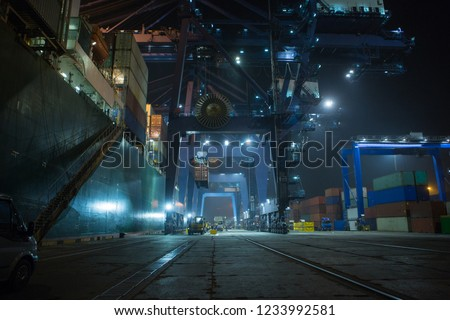 container terminal in industrial port with cranes.  Sea port container terminal during work at night in fog
