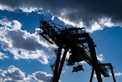 Container Terminal with the silhouette of a huge Cranes in Dortmund inland port harbour Germany on the ship canal. Transport Logistics technolology with blue sky, clouds and contrasting sunlight.