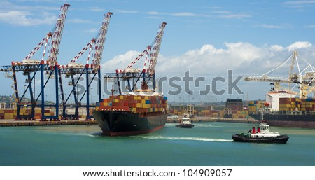 container vessel and a small ship, no logos on the photo leaving the port of Durban South Africa