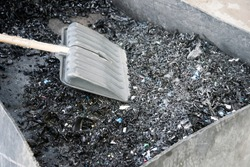 Container with crushed plastic at the factory. Shovel. Particles of crushed plastic are black in color. Plastic before melting. Reuse. The concept of caring for the environment.