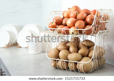 Container with potatoes and onions on grey kitchen counter, space for text. Orderly storage