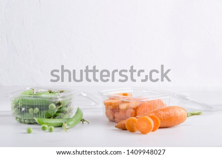 Containers for food full of fresh sweet slices of carrots and green peas in pods.Easy food.Empty space above for design