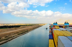 Containers loaded on deck of cargo container ship - side view. She is sailing through Suez Canal, on her international trade route.