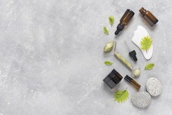 Containers of lotion, essential oils, massage rollers and gouache scraper on a gray concrete background. Natural SPA cosmetic products background. Layout of the beauty salon branding. Flat lay