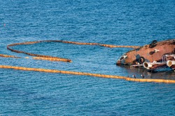 Containment Boom as Temporary Floating Barrier Used to Contain an Oil Spill After Tanker Wreck in Storm. Environmental Disaster Prevention Equipment