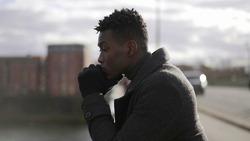 Contemplative African man looking at horizon wearing winter clothes