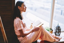 Contemplative Asian female 20s thinking at home interior holding interesting book, thoughtful hipster girl in bedclothes pondering on best seller spending leisure with hobby in comfortable apartment