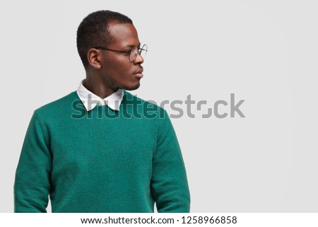 Contemplative black man focused aside with pensive expression, wears green fashionable sweater, stands over white background, blank space for your advertising content. Mae gazes on free space