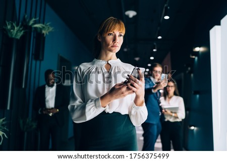 Contemplative female entrepreneur thoughtful looking away while making banking via smartphone device, pensive executive manager with mobile gadget thinking about business plan in office interior stock photo