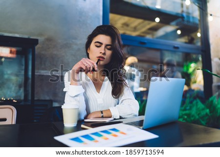 Contemplative female freelancer pondering on diagram statistics using laptop computer and documents for analyzing, thoughtful woman with netbook thinking during distance paperwork at street terrace Stock photo ©