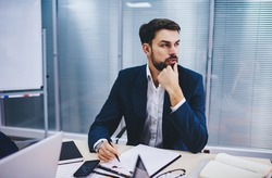 Contemplative male boss dressed in formal clothing sitting at table desk and thoughtful looking away while doing accounting job, pensive executive manager thinking about details of financial report