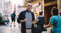 Contemplative male senior with travel map in hand choosing route way for exploring touristic city on vacations, pensive man thoughtful looking at street visiting new town during journey holidays