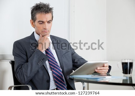 Contemplative mid adult businessman with hand on chin using digital tablet at desk in office