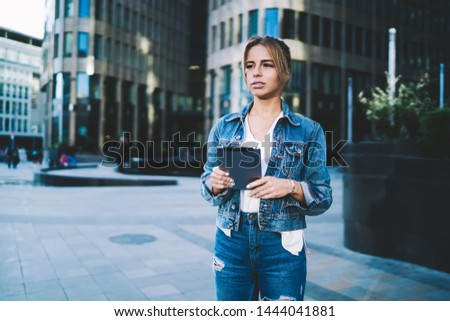 Contemplative millennial woman dressed in denim outfit thoughtful looking away with digital tablet in hands, attractive hipster girl in jeans spending time with modern technology on publicity area