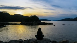 Contemplative woman sitting in a shore in front of the beautiful fjord of Saguenay at Petit-Saguenay